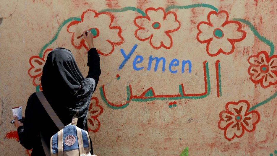A woman takes part in a graffiti painting campaign on a wall in Sanaa, Yemen