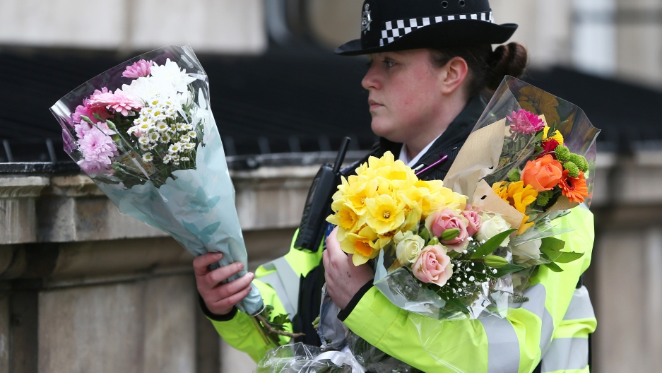 A police officer carries bouquets of flowers on Whitehall the morning after an attack in London.