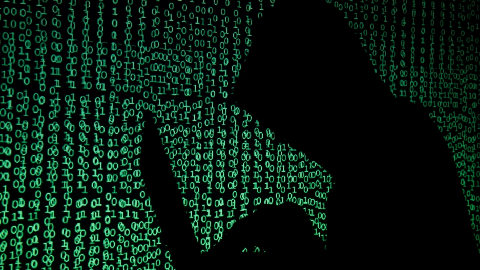 A hooded man sits on a computer in front of a screen of code.