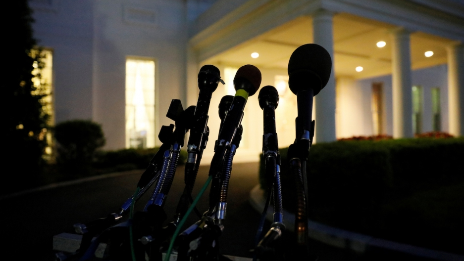 Microphones remain at the ready as night falls on the entrance of the West Wing