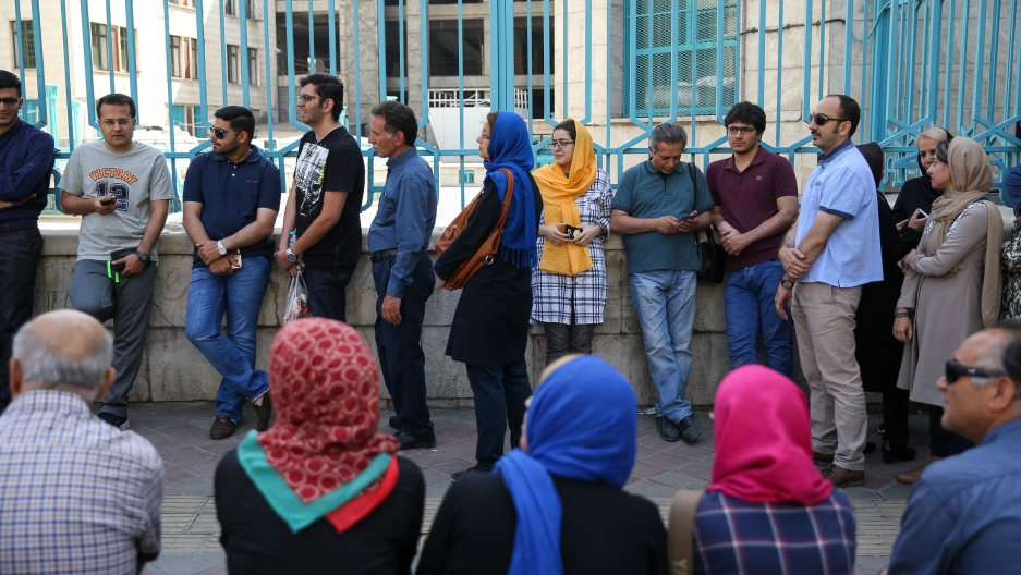 Iranians wait to cast their votes during the presidential election in Tehran Iran