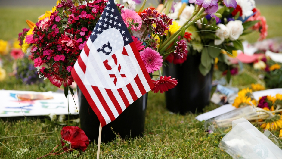 "A flag bearing an abbreviation for ""Portland"" stands at a makeshift memorial."