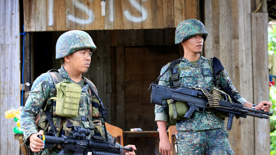 Soldiers stand guard along the main street of Mapandi village as government troops continue their assault on insurgents from the Maute group, who have taken over large parts of Marawi City.