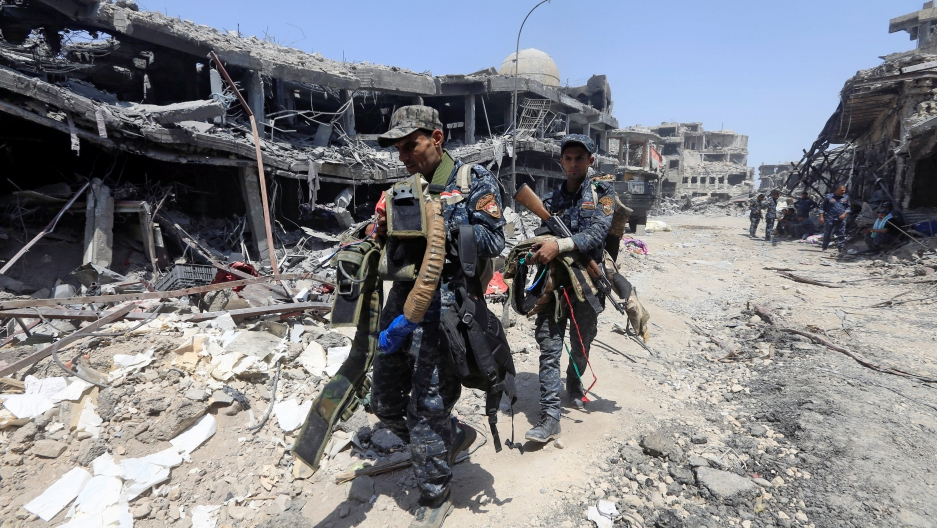 Members of Iraqi Federal police carry suicide belts used by Islamic State militants in the Old City of Mosul.