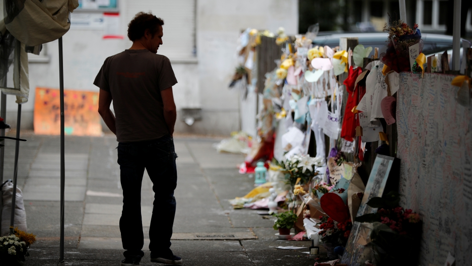 A man looks at floral tributes for the victims of the Grenfell Tower fatal fire, in London, Britain July 15, 2017.