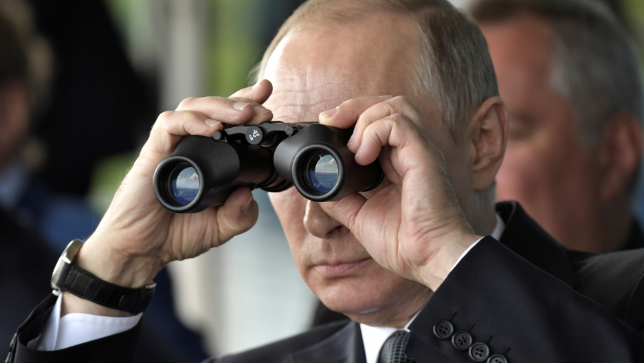 Russian President Vladimir Putin uses a pair of binoculars as he watches a display during the MAKS 2017 air show in Zhukovsky, outside Moscow.