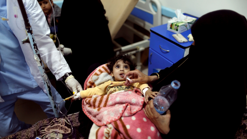Woman leans over hospital bed to give her daughter rehydration fluid at a cholera treatment center in Sanaa.