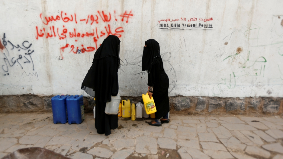 """Women fully covered in black carry jerrycans after they filled them up with drinking water from a charity tap, amid a cholera outbreak, in Sanaa. Graffiti on wall behind them reads """"USA kills Yemeni people."""""""