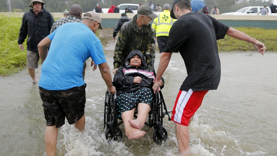 An elderly woman in a wheelchair is rescued from the flood waters of tropical storm Harvey in east Houston, Texas.