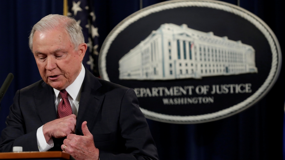 Man at podium with Department of Justice insignia behind him