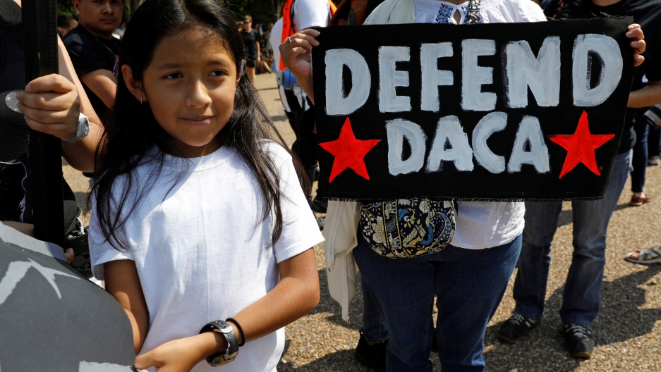 Demonstrators hold signs during a protest in front of the White House after the Trump administration on Tuesday scrapped the Deferred Action for Childhood Arrivals (DACA), a program that protects from deportation almost 800,000 young men and women who wer