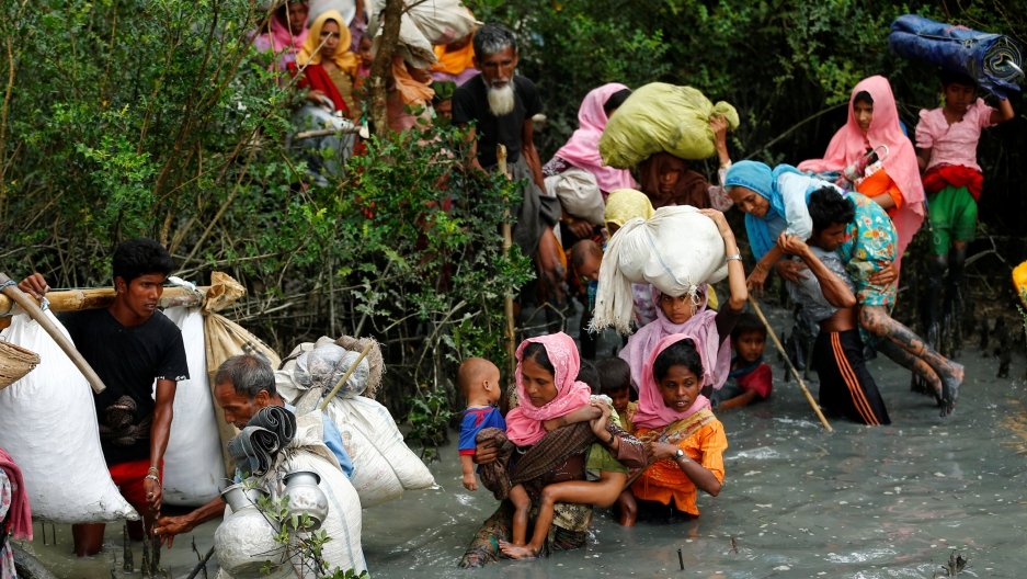 Rohingya refugees walk through water after crossing from Myanmar by boat through the Naf River in Teknaf, Bangladesh, on Sept. 7, 2017.