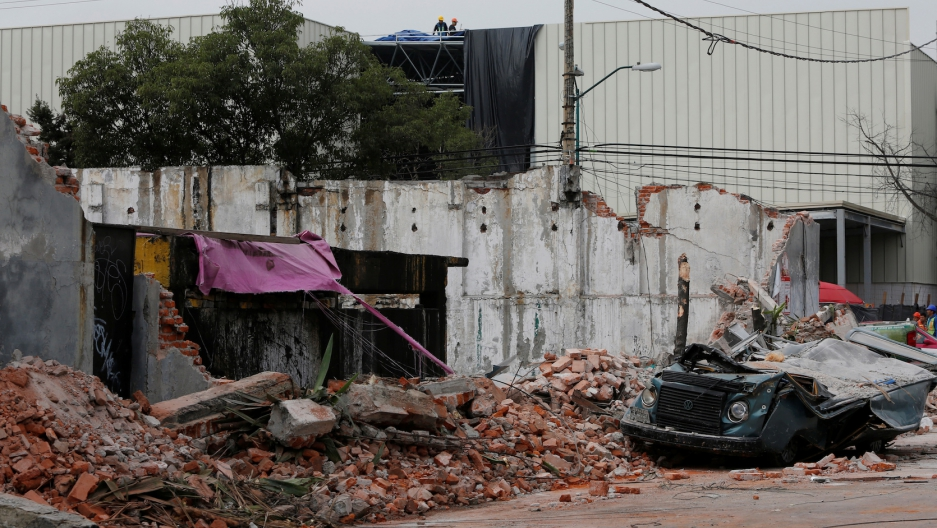 A damaged wall and a smashed vehicle are pictured after an earthquake in Mexico City on Sept. 8, 2017.
