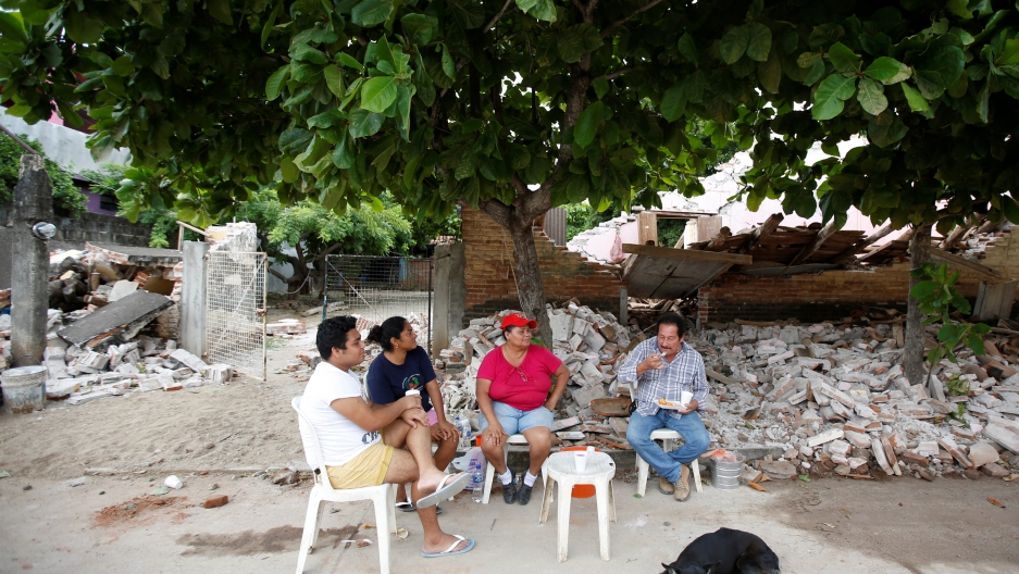 A family sits outside their house destroyed by the earthquake that struck the southern coast of Mexico late on Thursday, in Ixtaltepec, Mexico.