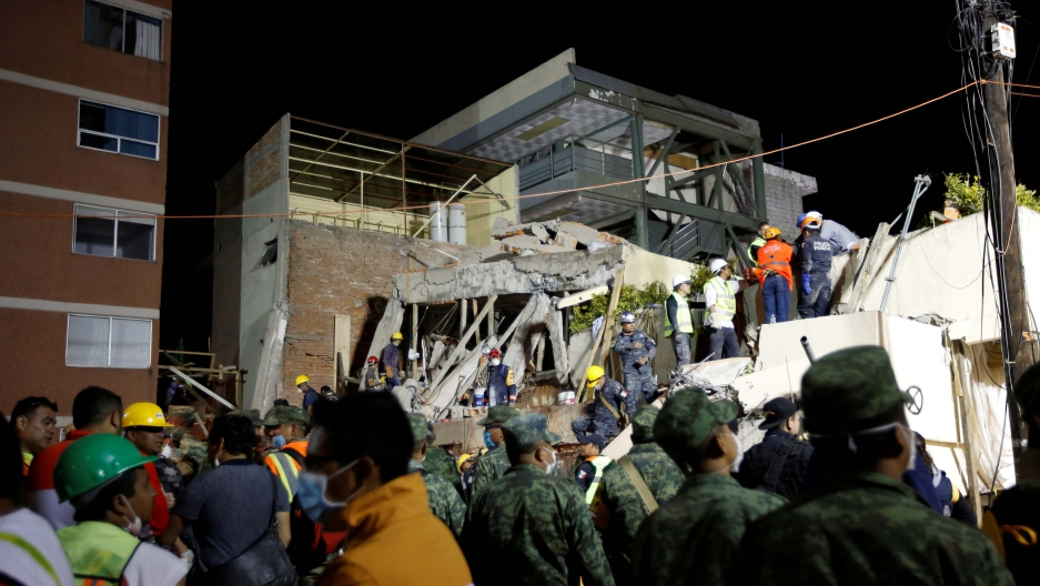 Rescue workers search through rubble during a floodlit search for students at Enrique Rebsamen school in Mexico City on Sept. 20, 2017.