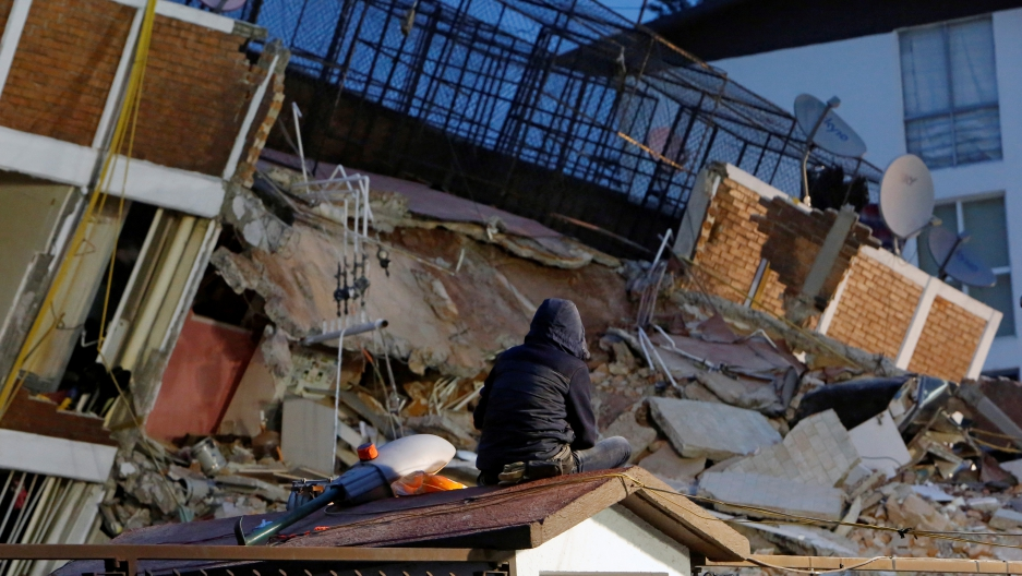 A person sits on the roof of a little house while looking at the rubble of a collapsed building after an earthquake hit Mexico City, Mexico September 20, 2017.
