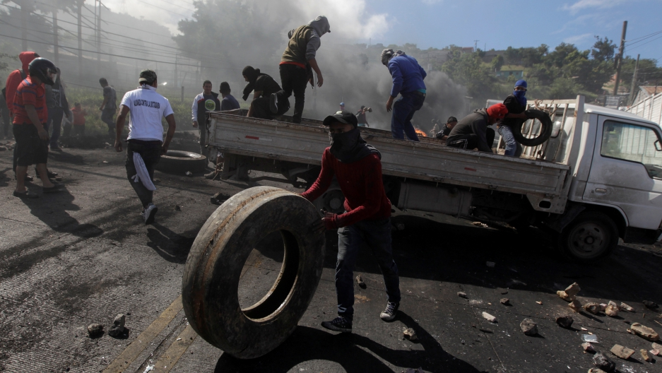 Supporters of Salvador Nasralla, presidential candidate for the Opposition Alliance Against the Dictatorship, unload a truck with rocks and tires for a barricade