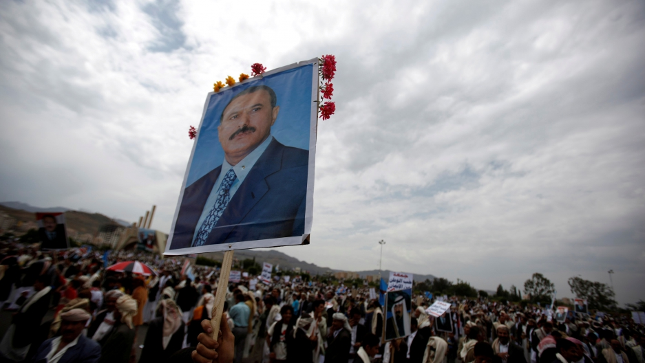 A supporter of Yemen's then President Ali Abdullah Saleh waves a poster featuring him during a rally to show support for him in Sanaa