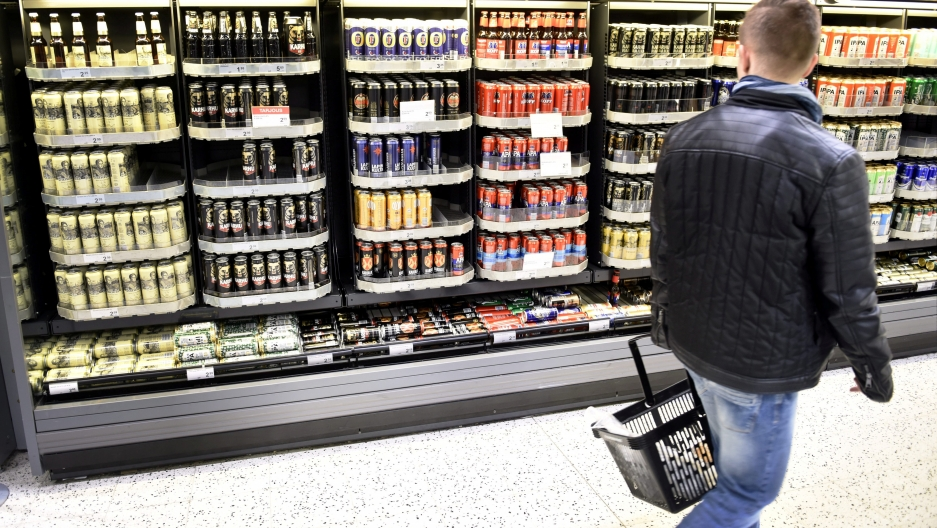 A man passes a shelf of beers on sale in a supermarket in Helsinki.