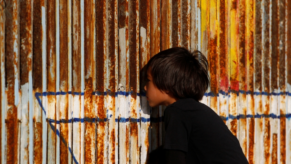 A child peers through the double steel fence that separates the US and Mexico, in Tijuana, last month