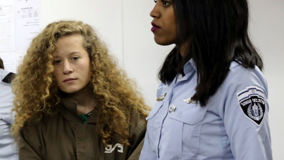 16-year-old Palestinian teen Ahed Tamimi enters a military courtroom escorted by Israeli Prison Service personnel at Ofer Prison near the West Bank city of Ramallah.
