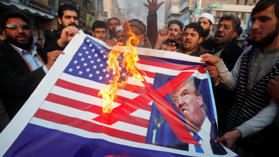 People burn a sign depicting a U.S. flag and a picture of U.S. President Donald Trump as they take part in an anti-U.S. rally in Peshawar, Pakistan, January 5, 2018.