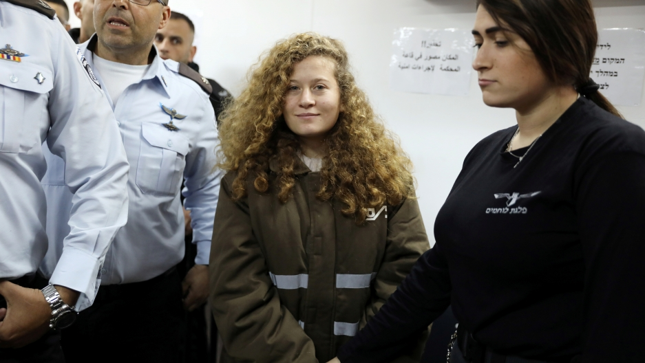 Palestinian teen Ahed Tamimi enters a military courtroom escorted by Israeli security personnel at Ofer Prison, near the West Bank city of Ramallah, Jan. 15, 2018.