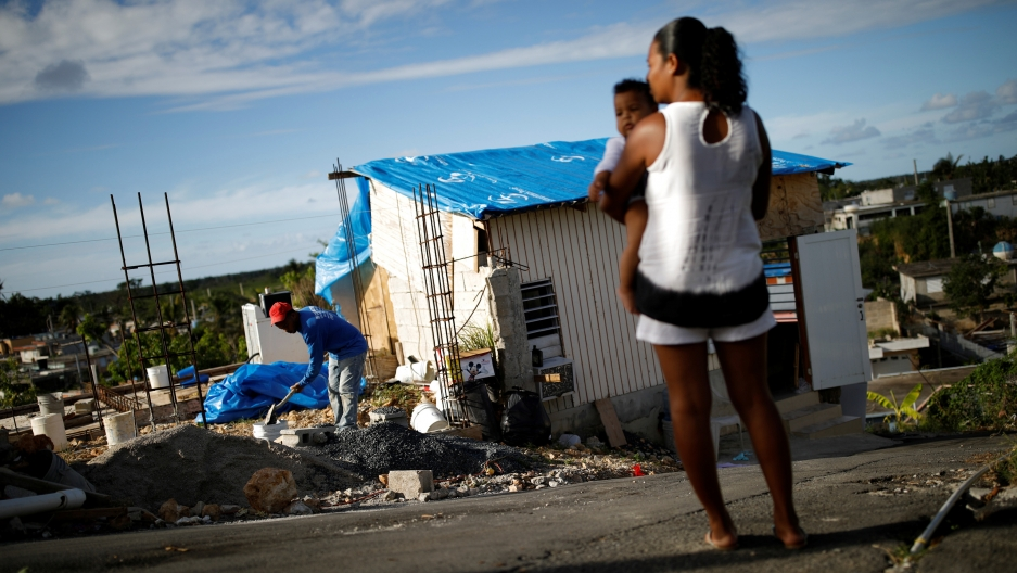 a woman holds a child in front of destroyed building
