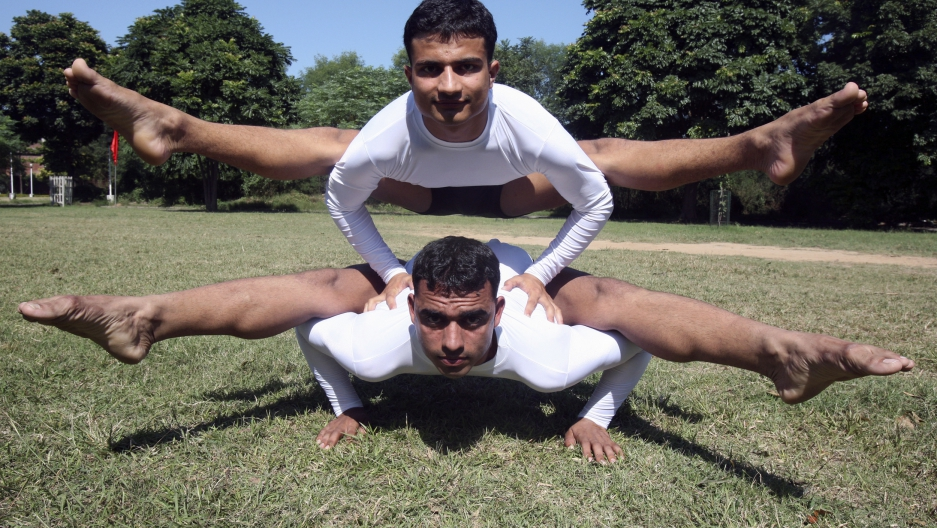 Two men perform difficult pose on grass lawn