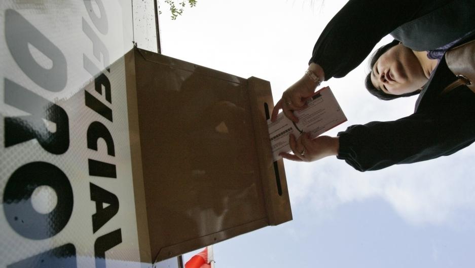 A woman drops her ballot off at a drop-off site
