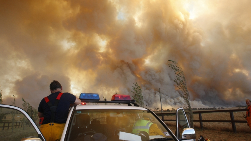"A fireman climbs down from his truck as a bushfire approaches a town outside of of Melbourne, Australia in February, 2009. Officials blamed the dozens of blazes across the country five years ago on a ""once in a century"" heatwave. With climate change incre"