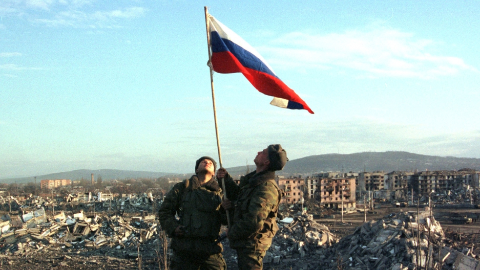 Russian soldiers raise the Russian flag over the rubble of Grozny, February 27th 2000.