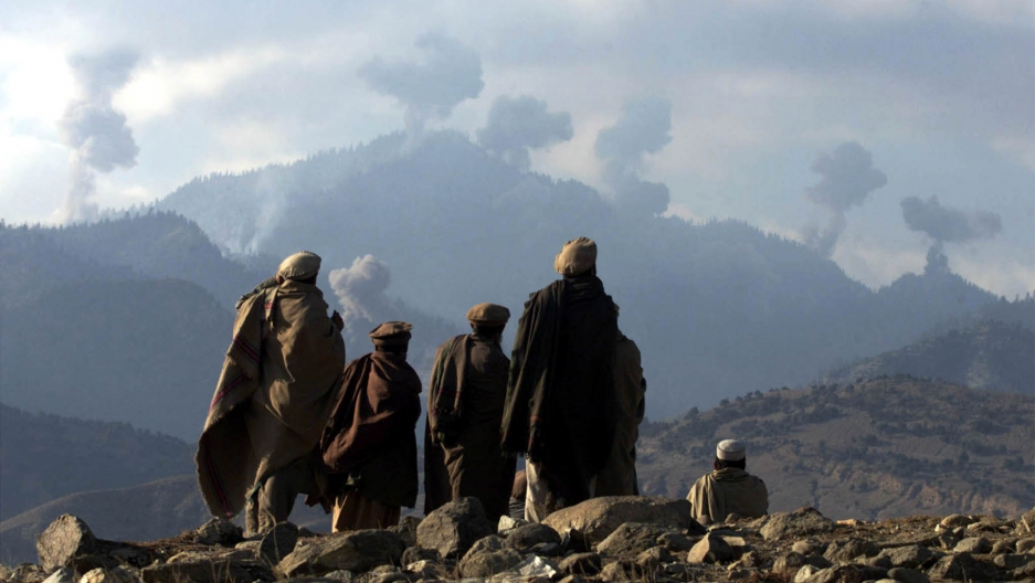 Anti-Taliban Afghan fighters watch several explosions from U.S. bombings in the Tora Bora mountains in Afghanistan December 16, 2001