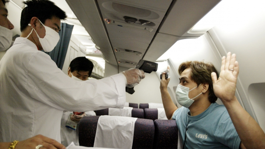 A Chinese doctor checks the temperature of a passenger on a flight from Hong Kong to Shanghai during the SARS outbreak in 2003. There are now fears that Ebola could spread via travel from West Africa to the rest of the world.