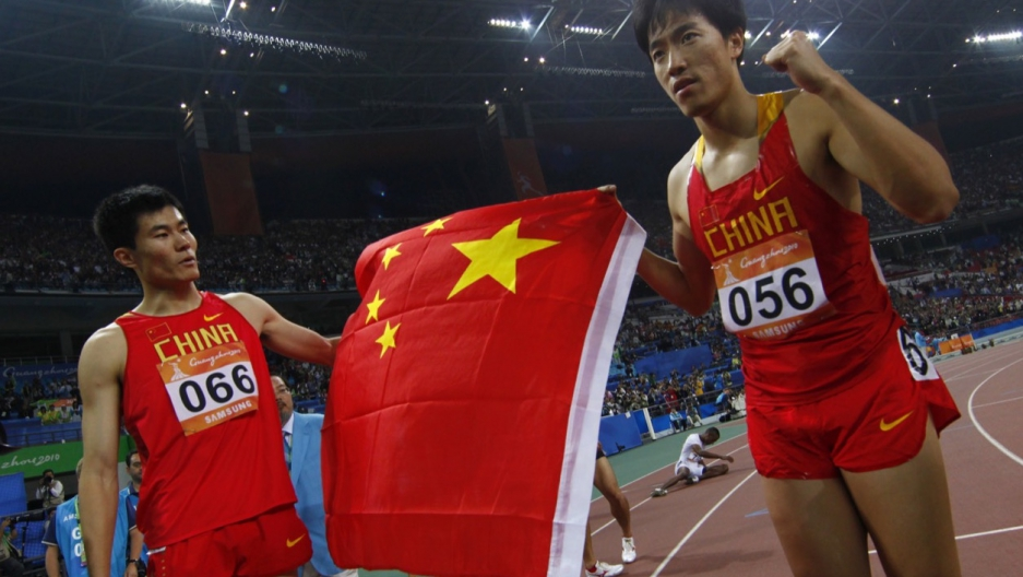 Chinese hurdler Shi Dongpeng, seen on the left after a race in the 2010 Asian Games in China, recenty reported being robbed in Rio.
