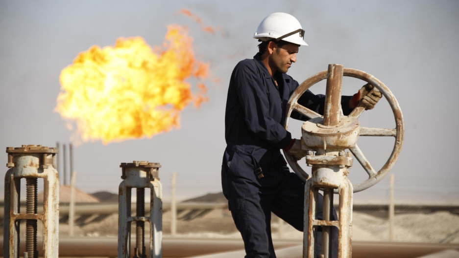 A worker adjusts the valve of an oil pipe at West Qurna oilfield in Iraq's southern province of Basra