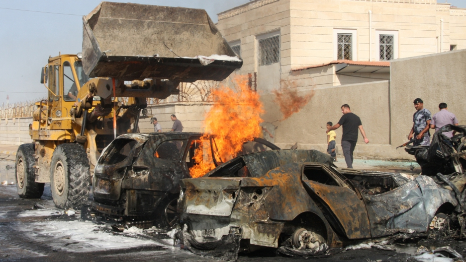 A bulldozer attempts to extinguish a fire in a destroyed vehicle at the site of a bomb attack in Baghdad.