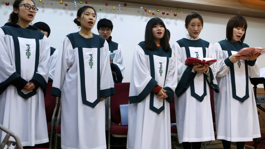 North Korean defectors living in Seoul, South Korea sing a hymn during a prayer service for peace and reunification of the divided Korean Peninsula in April 2013.