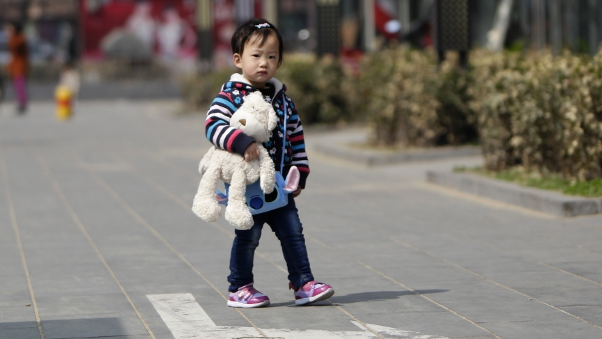 A girl walks along a street in Beijing. China has announced reforms to the policy of allowing most families to have only one child.
