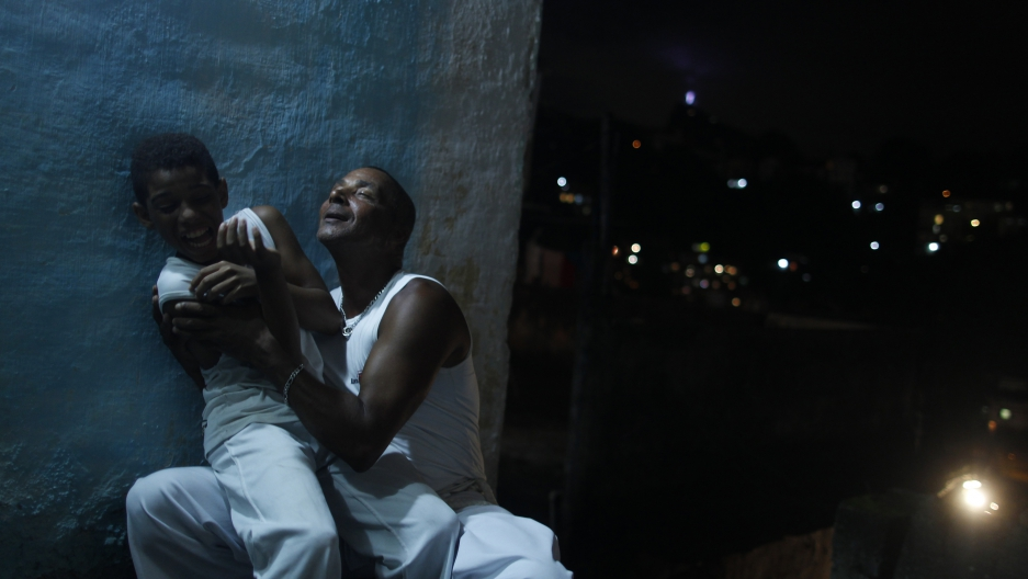 Blind capoeira teacher Joao Kanoa jokes with one of his students after giving classes at his home at the Fallet slum, in Rio de Janeiro March 2, 2013.