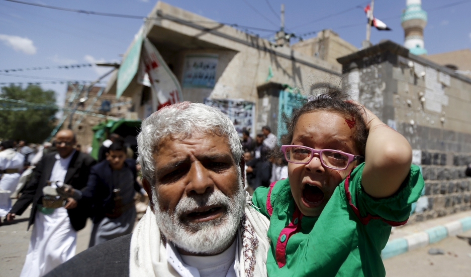 An injured girl reacts as she is carried by a man out of a mosque which was attacked by a suicide bomber in Sanaa on March 20, 2015.