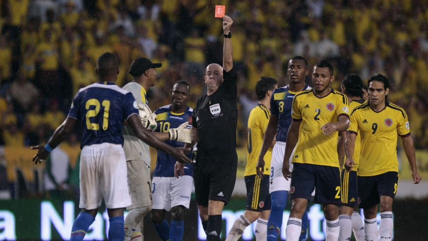 FIFA referee shows a red card during a 2014 World Cup qualifying match between Ecuador and Colombia
