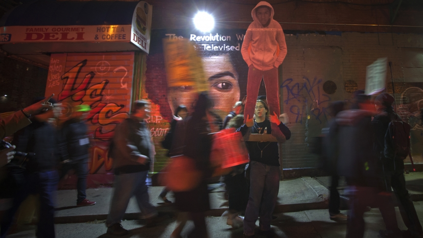 """A mural showing Gil Scott-Heron and his trademark phrase, """"The Revolution Will Not Be Televised,"""" is the backdrop for protesters marching through the streets of New York in 2012, demanding justice for slain Florida teenager Trayvon Martin."""