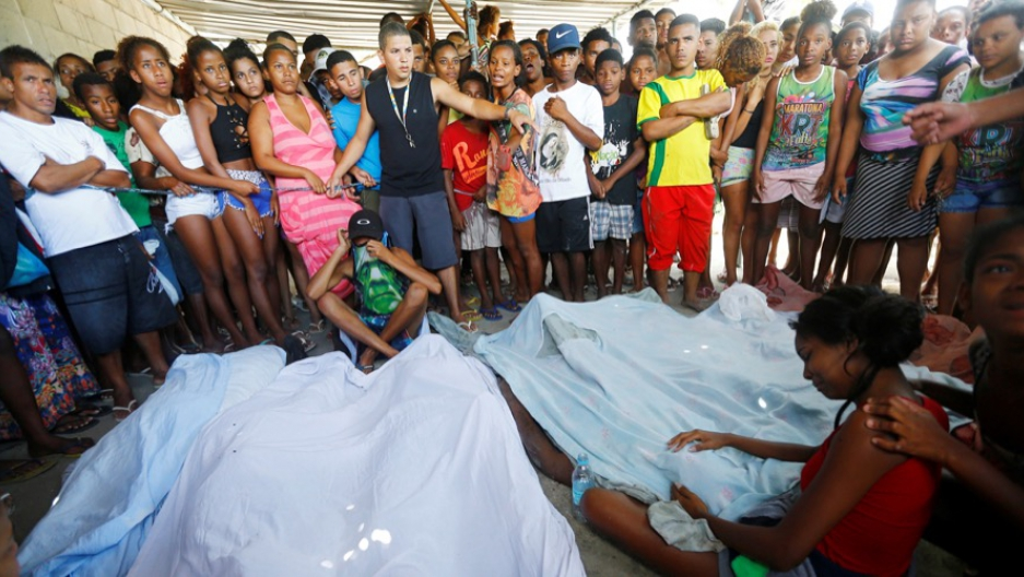 Residents gather round the bodies of suspected drug traffickers in the City of God favela in Rio de Janeiro on Nov. 20.
