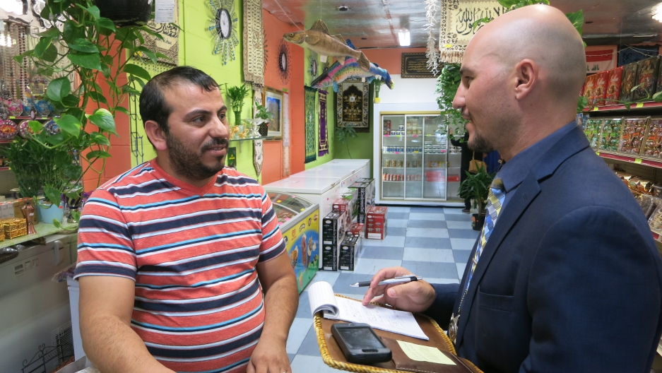 Officer Dustin Robinson (right) helps an Iraqi refugee shop owner in Boise.
