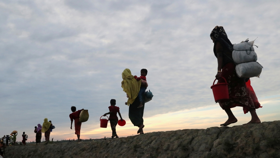 Rohingya refugees walk away from the photographer with their belongings in sacks on their backs.