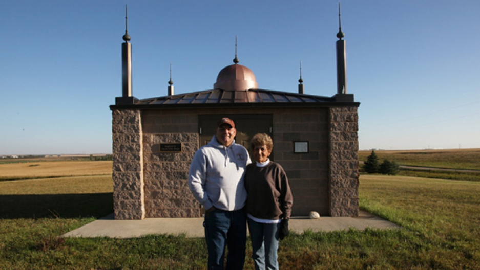 A couple stands in front of a replica of a small mosque