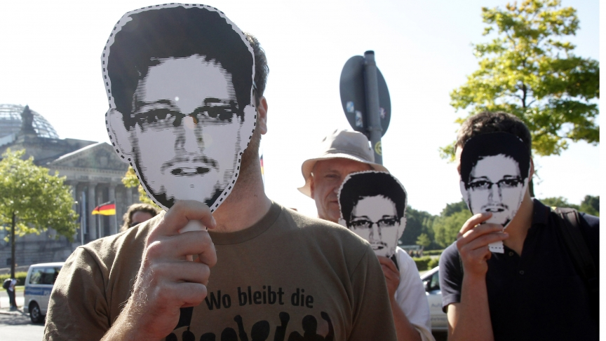 "Protesters hold masks depicting former US National Security Agency contractor Edward Snowden during a demonstration in Berlin on May 22, 2014. The sentence on the shirt reads, ""What has happened to revolution?"""
