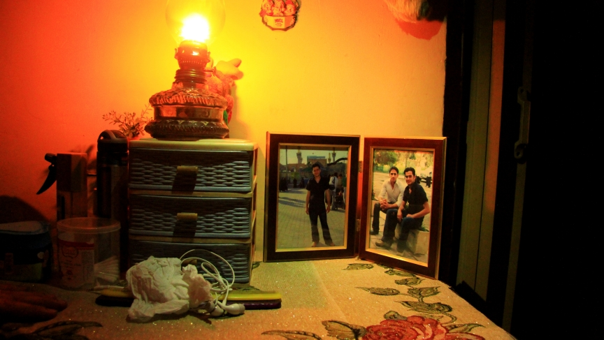 Photos of Salam and his older brother sit on a small table in his family's home, lit only by cell phones and a lantern. Salam says his brother was arbitrarily arrested by Iraqi security forces. The family was initially able to visit him, but it's been mor