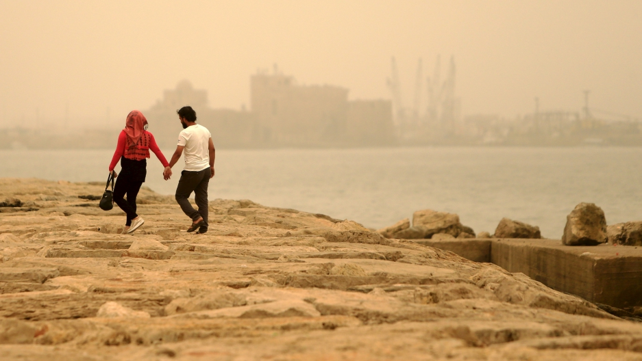 A couple walk during a sandstorm near the sea castle of the port-city of Sidon, Lebanon September 8.